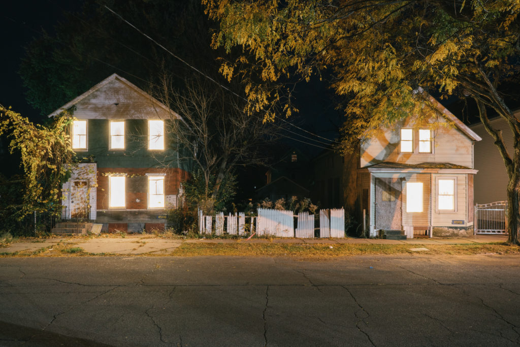 Two houses with lights behind the window in a dark street with a fence in between