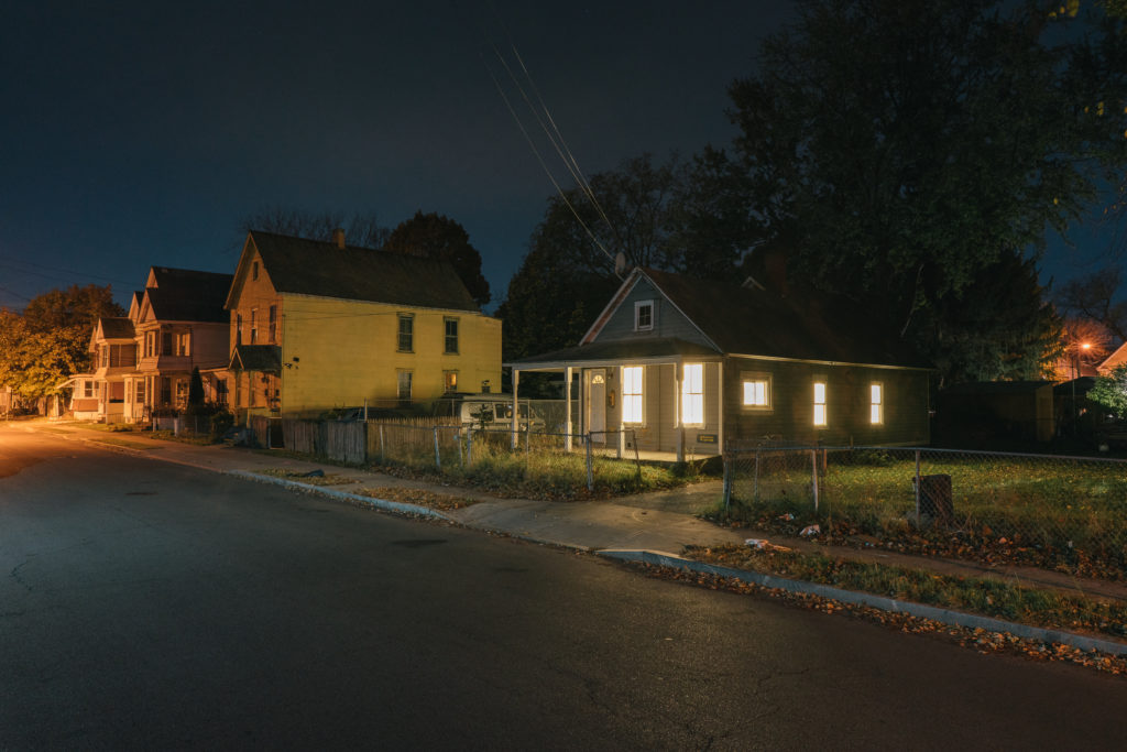 House with patio with lights behind the window in a dark street