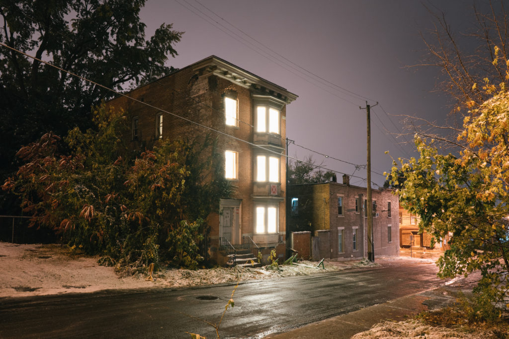 Three story building with lights behind the window in a dark street