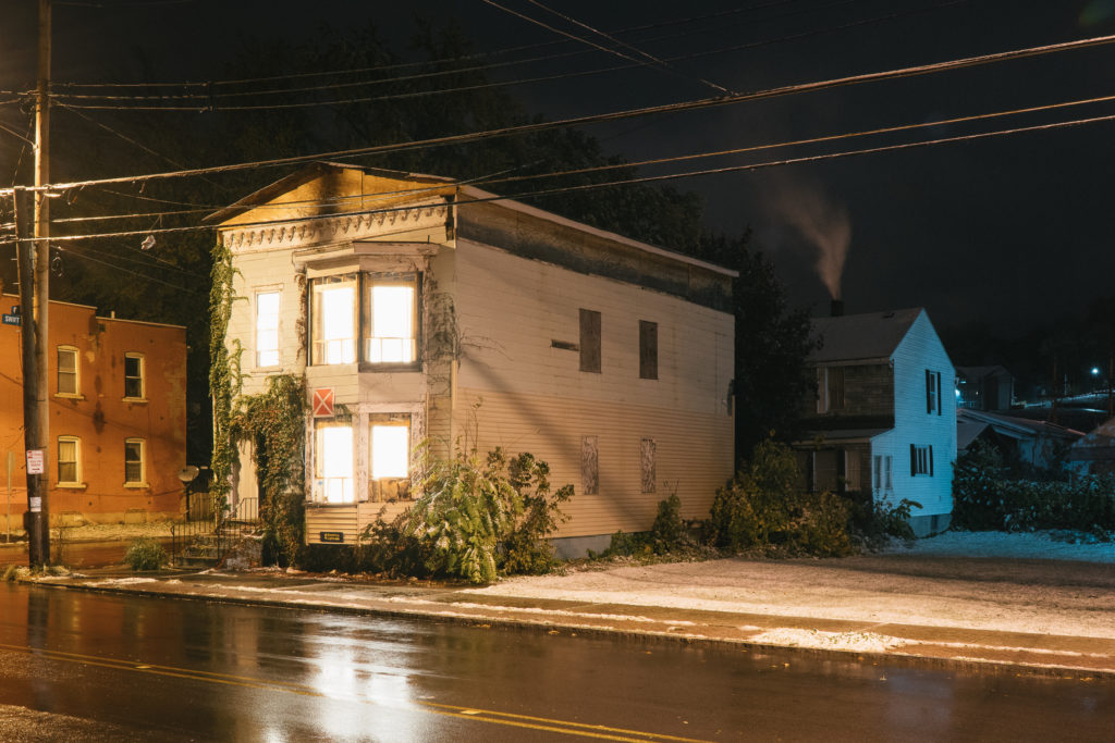 House with lights behind the window in a dark street