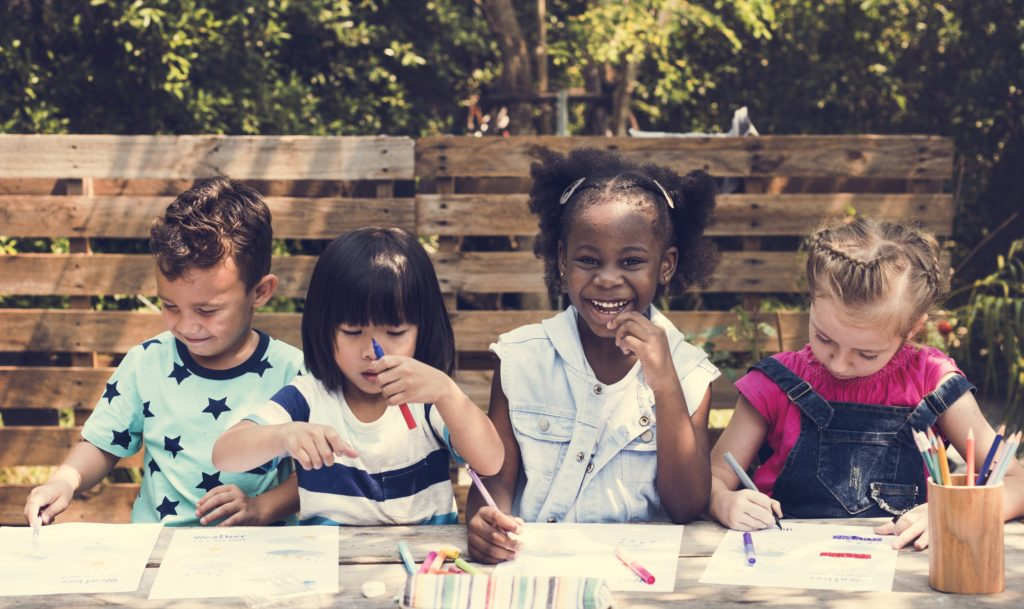 Four young children are drawing and learning at an outside table