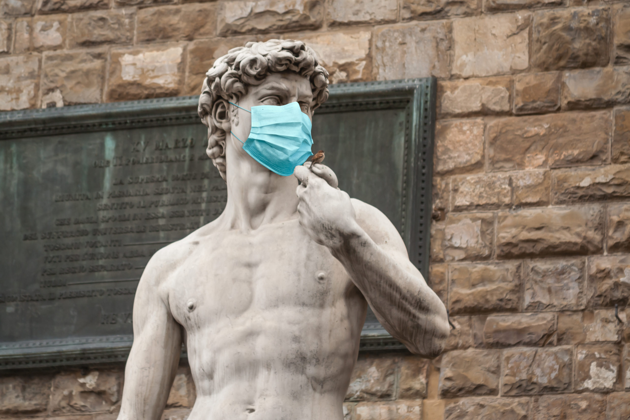 The Statue Of David in the Piazza della Signoria In Italy Wearing Blue Protective Medical Face Mask