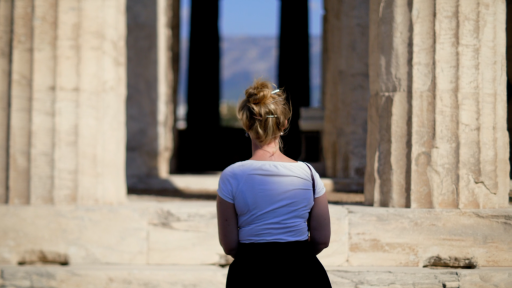A woman is looking at ancient Greek columns