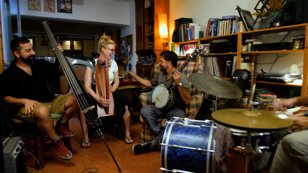 A group of musicians in a living room making music together