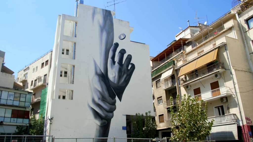 A mural of two hands holding each other in Greece.