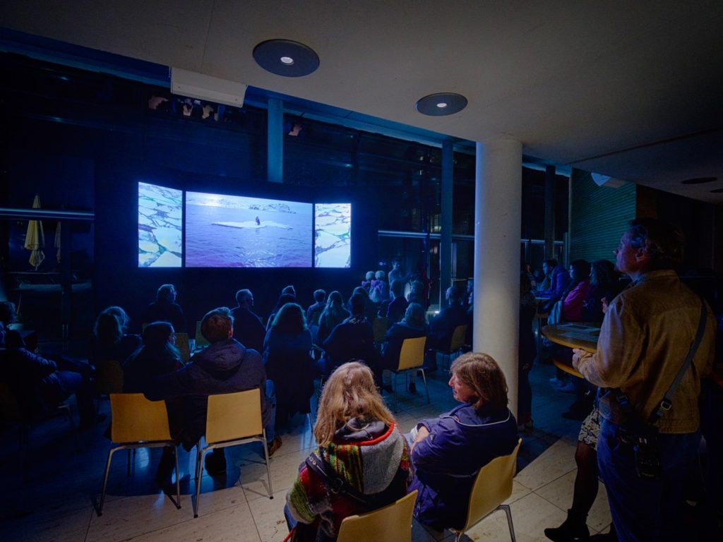 An audience watching the documentary film