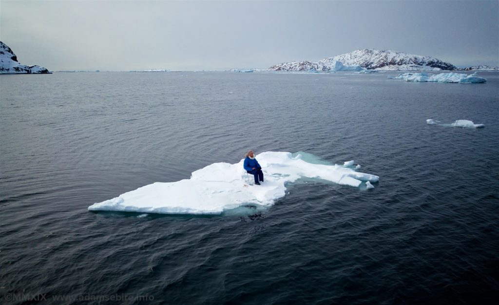 A man sitting on a chair on a small piece of ice in the middle of the sea