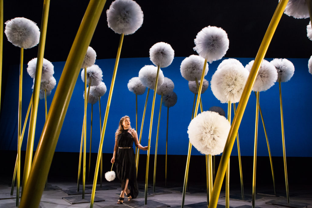 A singer surrounded by huge flowers on stage